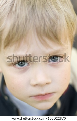 Portrait of a serious view of the sad little boy.