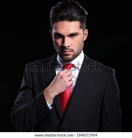 portrait of a serious young business man adjusting his tie while looking into the camera. on a black background - stock photo
