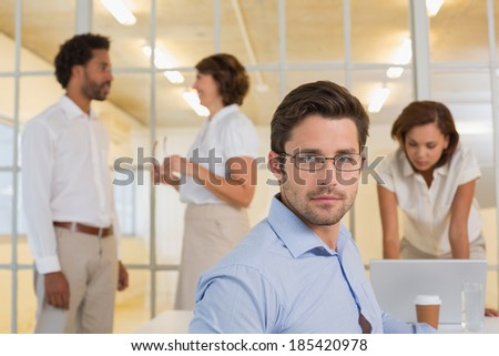 Portrait of a serious young businessman with colleagues in meeting at office - stock photo