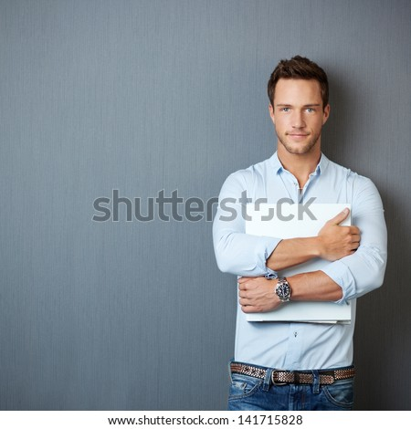 Portrait of a serious young man standing with binder against gray background - stock photo