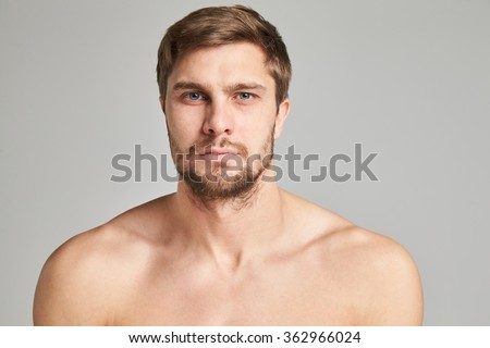 Portrait of a serious young man with bare shoulders on a gray background, powerful swimmers shoulders, beard, charismatic, adult, brutal, athletic - stock photo