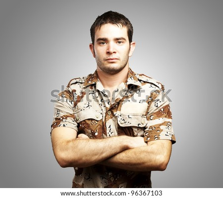 portrait of a serious young soldier standing against a grey background