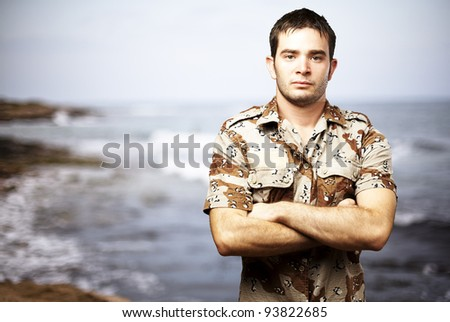 portrait of a serious young soldier standing against a sea background