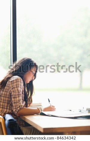 Portrait of a serious young student writing an essay in a library - stock photo