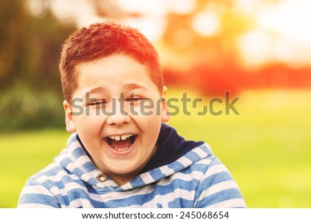 Portrait of a seven years old caucasian boy in the shirt with the blue and white stripes, laughing out loud, image taken in the park, with instagram style retro filter applied - stock photo