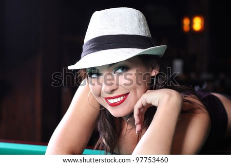 Portrait of a sexual girl in a white hat lying on the table for a game of billiards