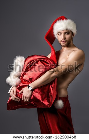 Portrait of a sexual young man in Christmas hat holding bag with gifts.  - stock photo