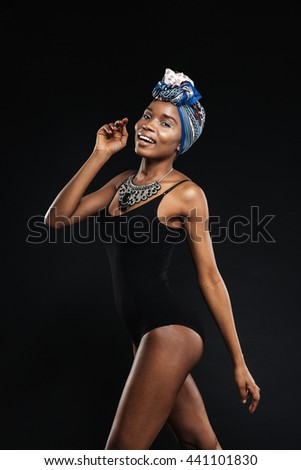 Portrait of a sexy african woman in black bodysuit posing isolated on a black background - stock photo