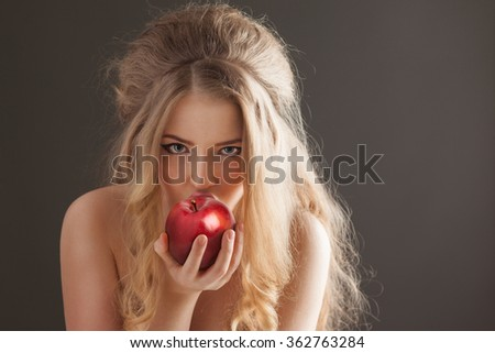 Portrait of a sexy beautiful nude pin-up girl from 60s or 70s, eating and biting a fresh red apple with temptation on dark background. - stock photo