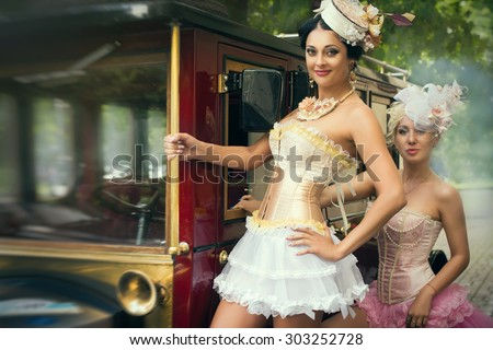 Portrait of a sexy beautiful women posing over retro car. Cabaret and pin-up concept. - stock photo