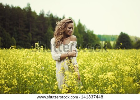Portrait of a sexy blond girl in a field of flowers - stock photo