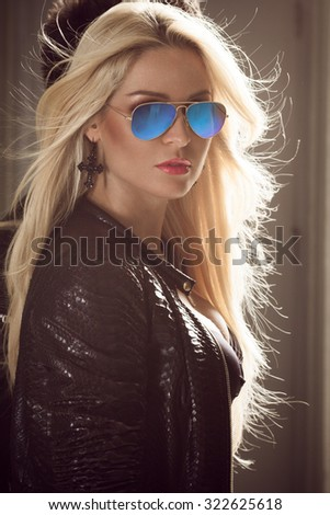 Portrait of a sexy blond woman in blue sunglasses - stock photo