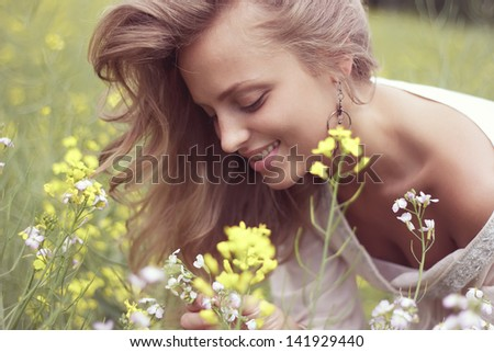 Portrait of a sexy blonde inhales the scent of flowers