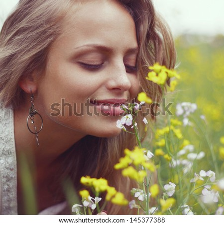 Portrait of a sexy blonde inhales the scent of flowers - stock photo