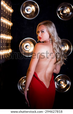Portrait of a sexy blonde who posing in long red dress on a dark background