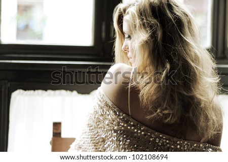 Portrait of a sexy blonde woman in window - stock photo