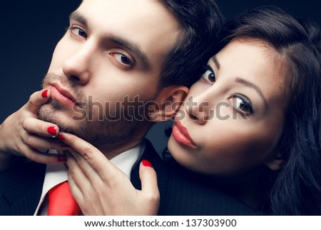 Portrait of a sexy couple, beautiful young man and woman posing over dark blue background. Classic style. Perfect hair and skin. Close up. Studio shot.