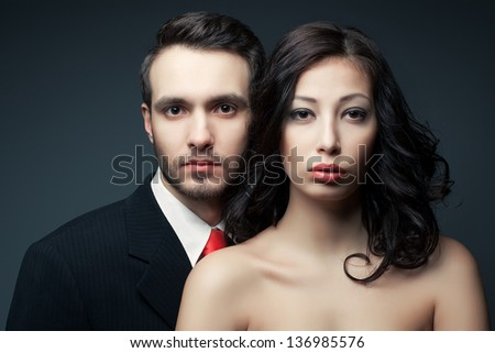 Portrait of a sexy couple, beautiful young man and woman posing over dark gray background. Classic style. Perfect hair and skin. Close up. Studio shot.