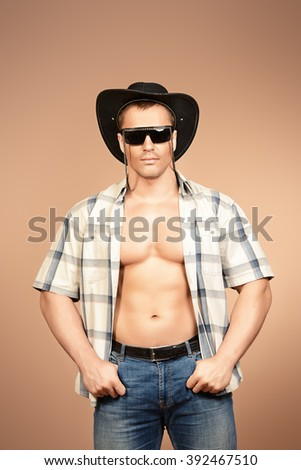 Portrait of a sexy cowboy man posing at studio. Western style. Denim, jeans. - stock photo