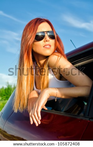 Portrait of a sexy girl out of car window - stock photo