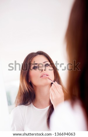 Portrait of a sexy girl putting make-up, looks in the mirror