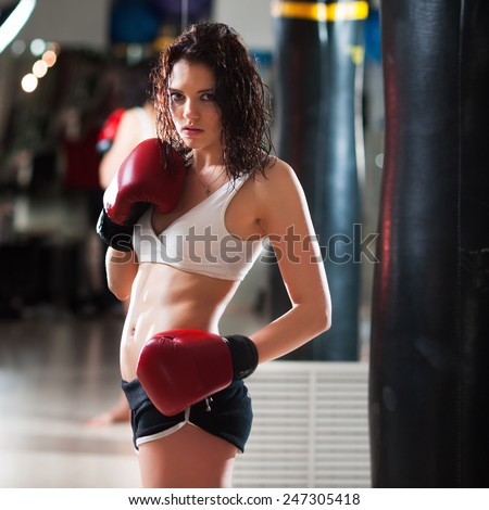 Portrait of a sexy hot female boxer standing by the punching bag - stock photo