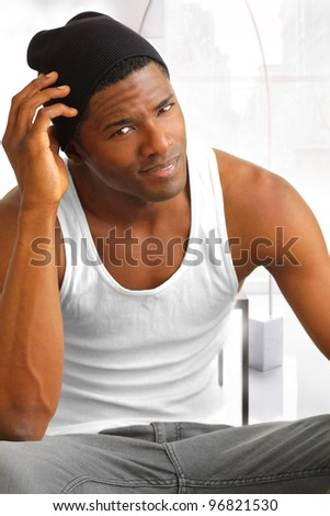 Portrait of a sexy male model in white tank and black hat in modern bright interior - stock photo