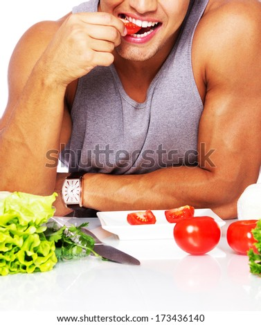 Portrait of a sexy man eating on the kitchen - stock photo