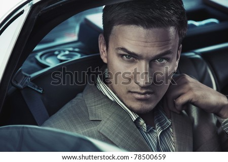 Portrait of a sexy man in the car - stock photo