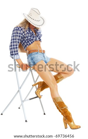 Portrait of a sexy model posing in cowgirl clothing posing on a chair - stock photo