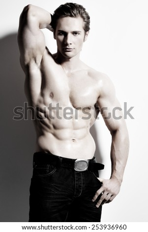 Portrait of a sexy muscular handsome man with hands behind head posing on a white background. - stock photo