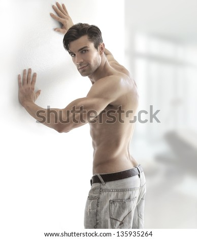 Portrait of a sexy muscular shirtless man turning in bright modern setting with copy space - stock photo