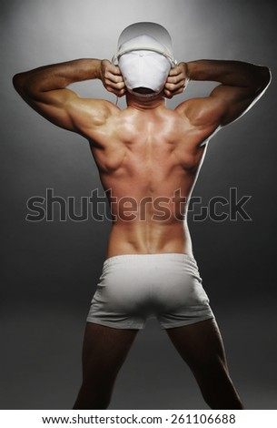 Portrait of a Sexy Topless Athletic Man Showing his Back Muscles with Tattoo on a Gray Background. - stock photo