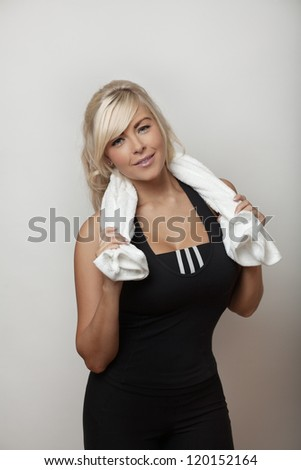 portrait of a sexy woman after a workout with a towel over her shoulder holding a bottle of water - stock photo