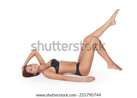 Portrait of a sexy woman lying down provocatively in a studio wearing black lingerie - stock photo
