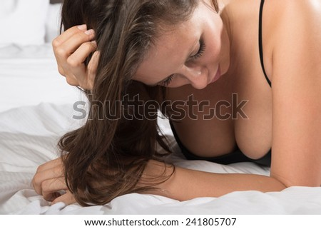 Portrait of a sexy woman lying on a bed