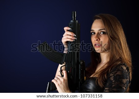 Portrait of a sexy woman posing with gun - stock photo