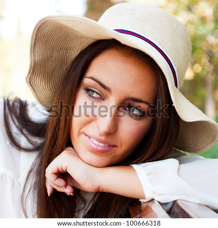 Portrait of a sexy young female smiling in a park while sitting on bench and looking away - Outdoor - stock photo