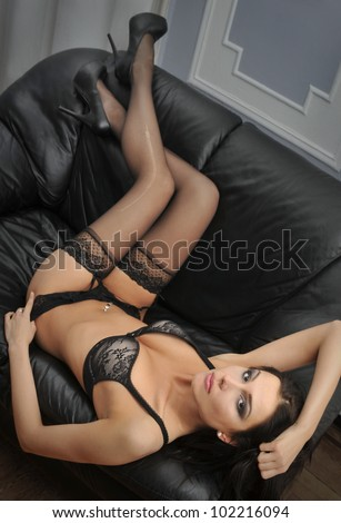 Portrait of a sexy young lady looking confidently in lingerie at black sofa bed - stock photo