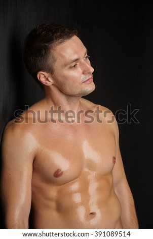 Portrait of a sexy young man leaning against grey wall - stock photo