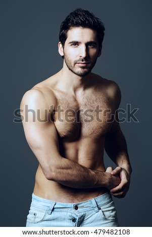 Portrait of a sexy young man with perfect muscular body slightly smiling invitingly at camera. Gray background. Studio shot.