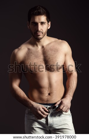 Portrait of a sexy young man with perfect muscular body smiling invitingly at camera. Black background. Studio shot. - stock photo