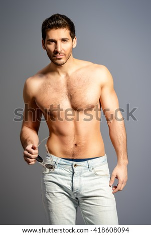 Portrait of a sexy young man with perfect muscular body smiling invitingly at camera. Gray background. Studio shot.
