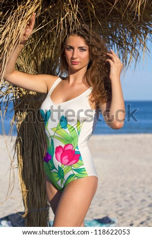 Portrait of a sexy young woman on beach near the palm tree