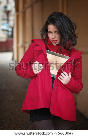 Portrait of a sexy young woman showing bust on digital tablet - stock photo