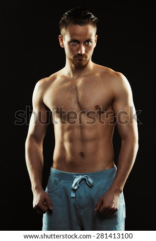 Portrait of a shirtless confident young athletic man standing against black background - stock photo