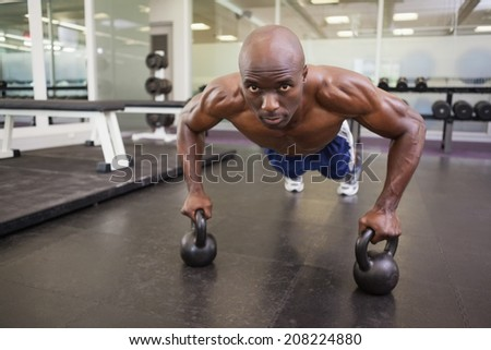 Portrait of a shirtless muscular man doing push ups in gym - stock photo