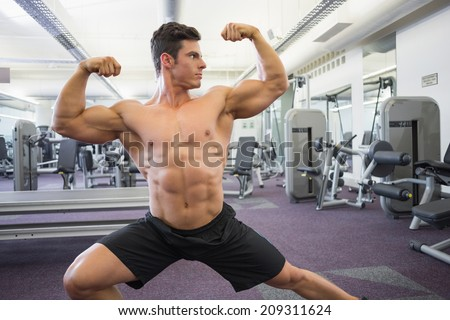 Portrait of a shirtless muscular man flexing muscles in gym - stock photo
