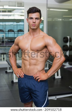 Portrait of a shirtless muscular man posing in gym - stock photo
