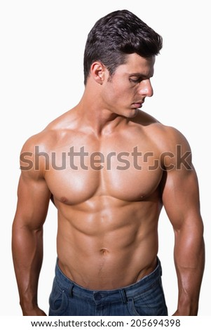 Portrait of a shirtless muscular man standing over white background